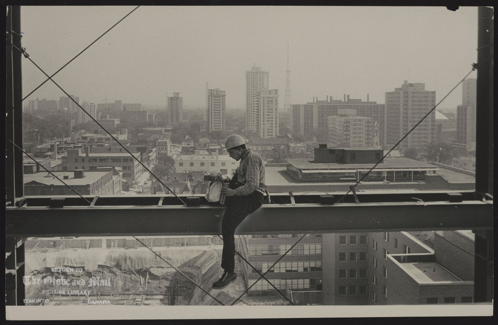The notes transcribed from the back of this photograph are as follows: CONSTRUCTION Perched comfortably on a girder with a magnificent view of Toronto around him, steel worker Walter Stein, a commuter from Keswick, enjoys solitary lunch on rapidly rising Queen's Park project. Four towers will house 9,000 civil servants working in scattered location in Toronto.