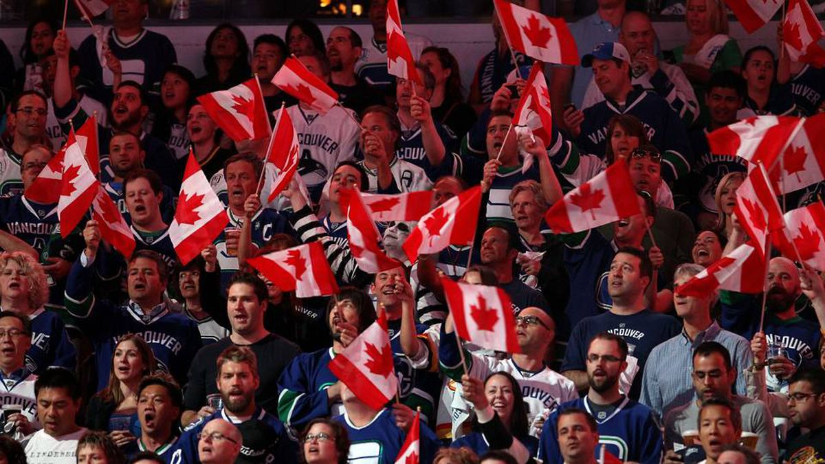 Fans wave the Canadian Flag during Game 5 of the 2011 NHL Stanley Cup Final at Rogers Arena.