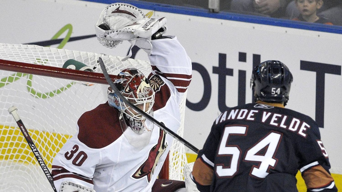 Phoenix Coyotes' goalie Ilya Bryzgalov (L) makes a glove save as Edmonton Oilers' Chris Vande Velde looks for a rebound during the second period of their NHL hockey game in Edmonton March 17, 2011.