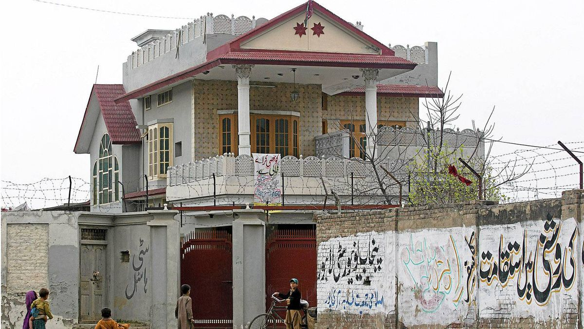 In this photo taken Thursday, March 8, 2012, Afghan refugees gather outside the house in Haripur, Pakistan, that Pakistan's intelligence agency believes Osama bin Laden lived in for nearly a year until he moved into the villa where he was eventually killed.
