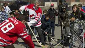 Stephen Harper plays ball hockey with a group of youngsters in Ottawa on Sunday, April 3, 2011
