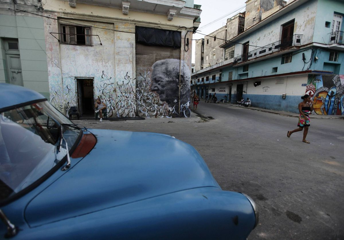 People walk past a creation by Cuban-American artist Jose Parla and French artist J.R. on a street wall in Havana for the upcoming 11th Havana Biennial contemporary art exhibition.