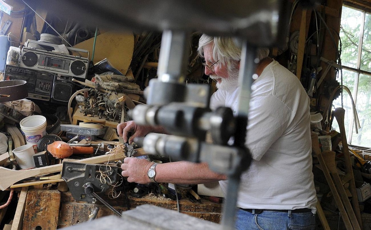 Seen through a band saw in his workshop, Bill Miller shaves a paddle into shape. As well as canoes, Mr. Miller makes paddles to fit the custom orders he receives.