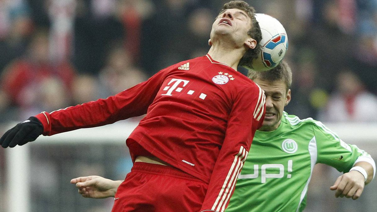 Bayern's Thomas Mueller, foreground, and Wolfsburg's Marco Russ challenge for the ball during the German first division Bundesliga soccer match between FC Bayern Munich and VfL Wolfsburg in Munich, southern Germany, on Saturday, Jan. 28, 2012. (AP Photo/Matthias Schrader)