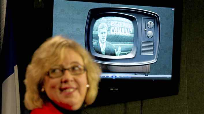 Green party leader Elizabeth May unveils their attack ad on attack ads during a press conference on Parliament Hill in Ottawa on Monday, March 7, 2011. Prime Minister Stephen Harper can be seen in the ad being viewed during the realse.