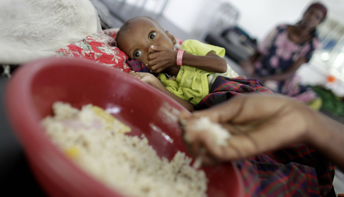 A mother eats a rice mixture as a child looks on in the backgorund. The children should not eat the rice, but when they begin to reach for it it is a sign that their appetite is returning, and they are moved to another area to continue treatment.