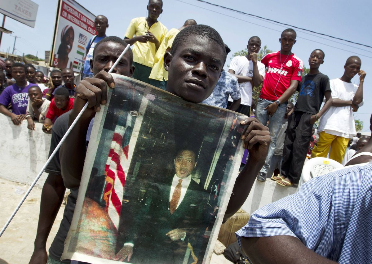A man holds an old portrait of Charles Taylor at an area where people gathered in the Sinkor neighborhood of Monrovia. Isolated groups gathered wherever they could find a working television to watch the verdict being announced by the special international tribunal on Sierra Leone in the case against former Liberian President Charles Taylor.