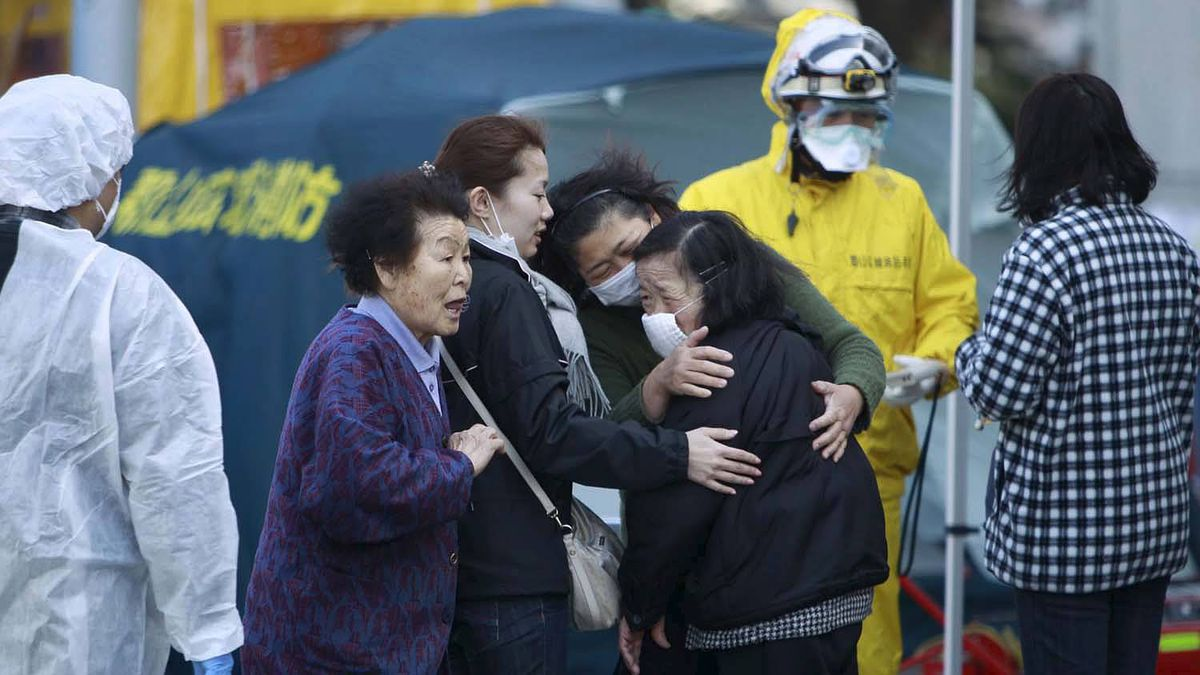 Residents evacuated from areas surrounding the Fukushima nuclear facilities damaged in Friday's massive earthquake react during a check for radiation contamination, Sunday, March 13, 2011, in Koriyama city, Fukushima prefecture, Japan.