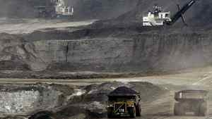 Mining trucks carry loads of oil-laden sand at the Albian Sands oils sands project in Fort McMurray, Alta.