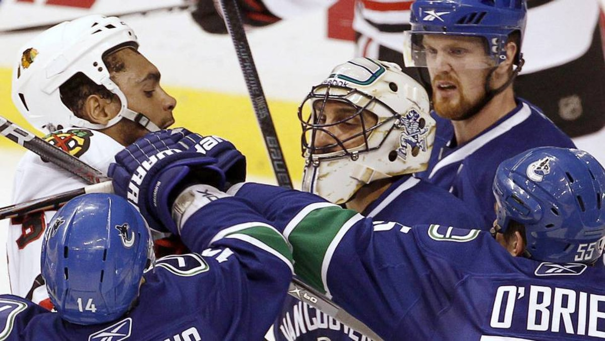 Chicago Blackhawks right wing Dustin Byfuglien crashes into Vancouver Canucks goalie Roberto Luongo as Alex Burrows, Shane O'Brien and Henrik Sedin come to assist in the third period during Game 3 of their NHL Western Conference semi-final hockey game in Vancouver, British Columbia May 5, 2010.