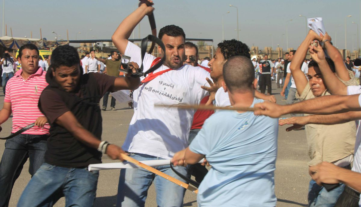 Egyptians loyal to the former president strike a foe during the trial of officials from the ousted government outside police academy where the opening of their trial is taking place on the outskirts of Cairo.