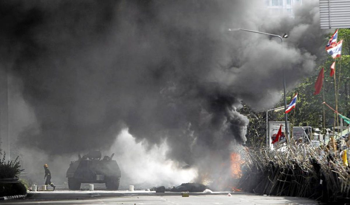 """An armoured vehicle is obscured by smoke from a burning barricade during an operation to evict anti-government """"red shirt"""" protesters from their encampment in Bangkok on May 19, 2010."""