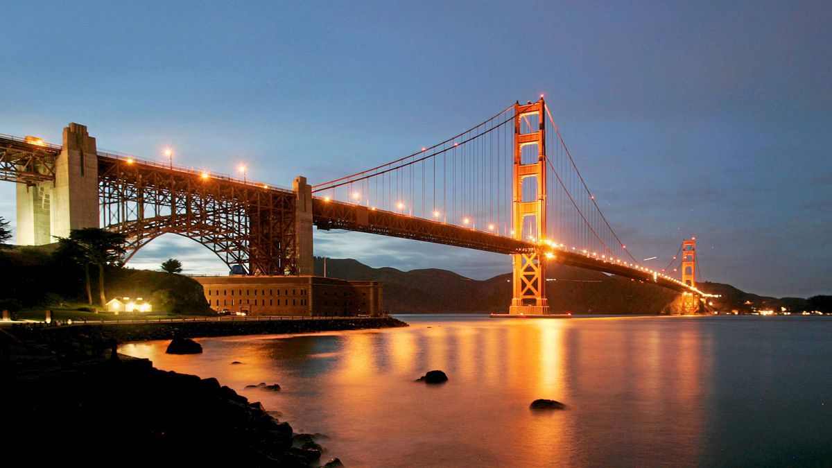 The Golden Gate Bridge is lit at dusk at Fort Point in San Francisco.