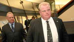 Doug Ford, left, follows Rob Ford to a media conference at City Hall in November.