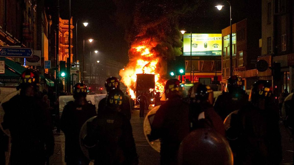 A double decker bus burns as riot police try to contain a large group of people on a main road in Tottenham, north London on 6 August 2011.