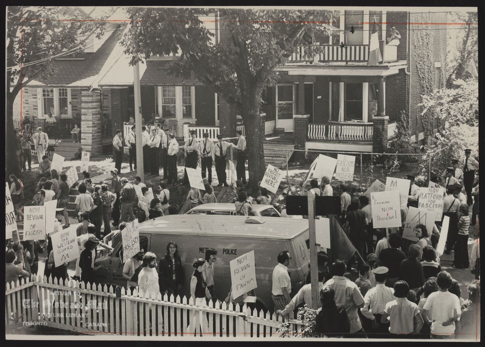 The notes transcribed from the back of this photograph are as follows: Police stand in front of Ashdale Avenue house occupied by Western Guard Party while about 100 members of United Front march in the street.