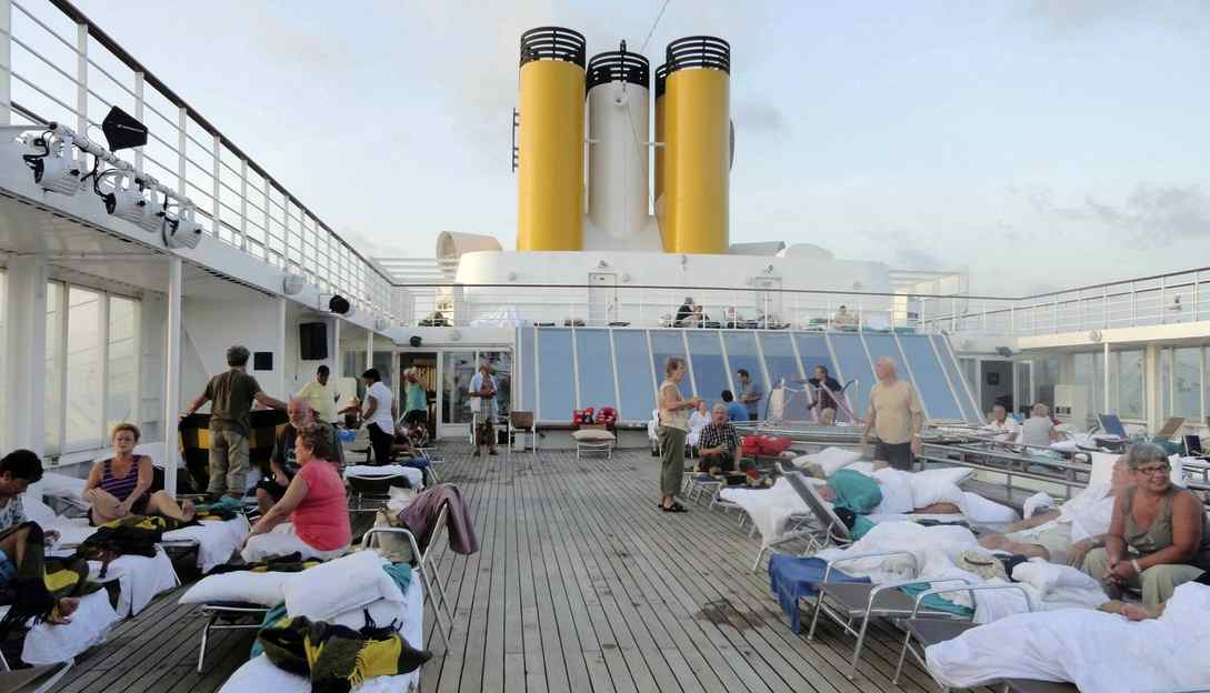 In this image taken on Tuesday, Feb. 28, 2012 by a passenger of the Costa Allegra cruise ship, passengers sit on the deck of the ship. A disabled cruise ship carrying more than 1,000 people docked in the island nation of the Seychelles Thursday after three days at sea without power since a fire broke out in the generator room on Monday.