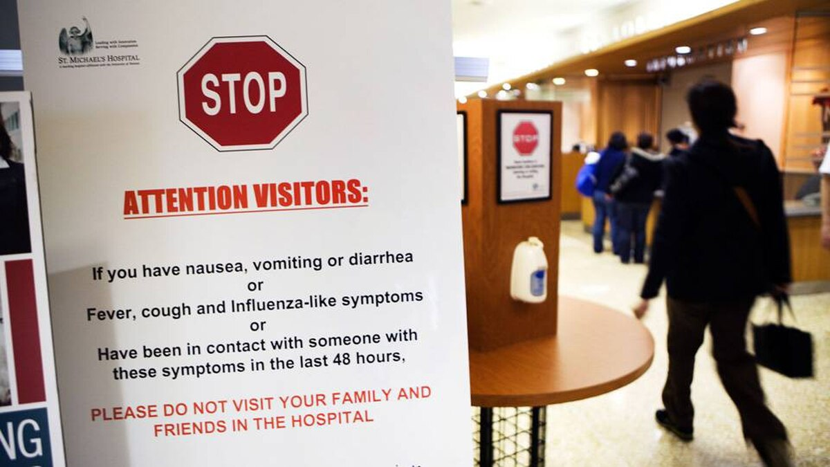 People walk by a sign inside St. Michael's Hospital in Toronto