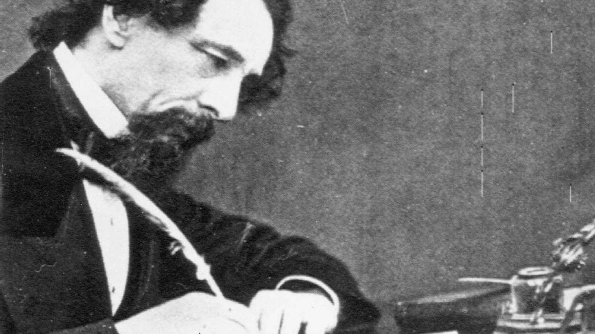Novelist Charles Dickens at his writing desk, c. 1859.