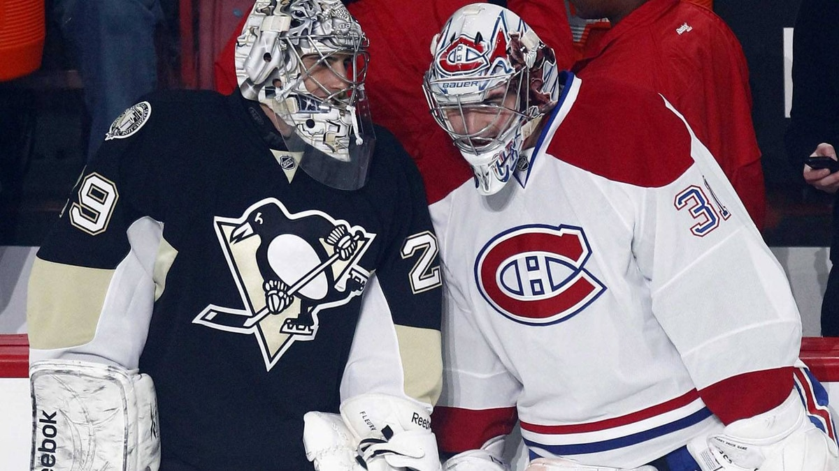 Pittsburgh Penguins goalie Marc- Andre Fleury (L) talks to Montreal Canadiens goalie Carey Price (R) behind Carolina Hurricanes goalie Cam Ward during the NHL All-Star hockey skills competition in Raleigh, North Carolina, January 29, 2011. REUTERS/Shaun Best