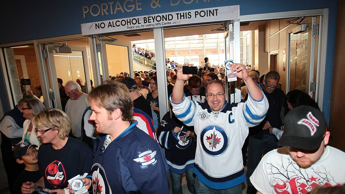 Winnipeg Jets fans celebrate as they are the first to go through the doors into the MTS Centre before the Winnipeg Jets game against the Montreal Canadiens before NHL action at the MTS Centre on October 9, 2011 in Winnipeg, Manitoba, Canada. The game is Winnipeg's first NHL regular season game in 15 years. (Photo by Marianne Helm/Getty Images)