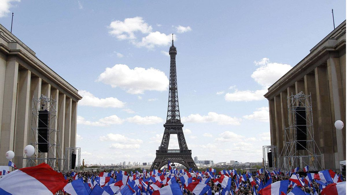 Supporters wave flags as they wait for Nicolas Sarkozy, to deliver his speech at Trocadero square during a campaign rally in front of the Eiffel Tower in Paris May 1, 2012.