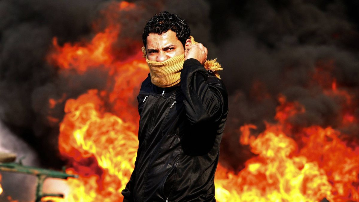 A protester stands in front of a burning barricade during a demonstration in Cairo Jan. 28, 2011.