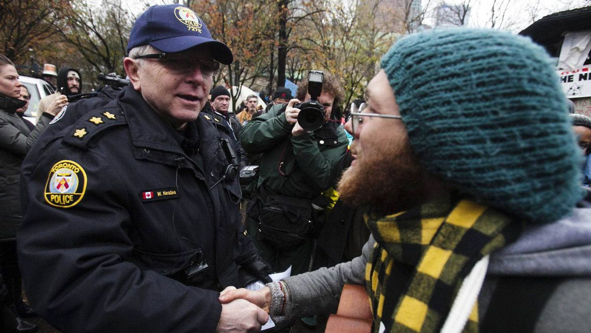 "A police officer shakes hands with a protester in St. James park after they moved in to evict protesters during the ""Occupy Toronto"" movement in Toronto, November 23, 2011."