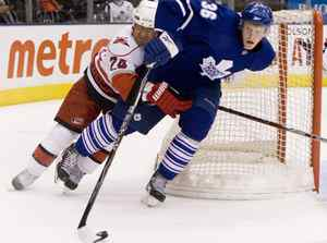 Toronto Maple Leafs defenceman Carl Gunnarsson (right) controls the puck despite pressure from Carolina Hurricanes Scott Walker during third period NHL action in Toronto on Tuesday, March 2, 2010. THE CANADIAN PRESS/Chris Young