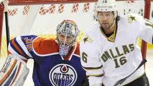 Dallas Stars Adam Burish, right, tries to screen the Edmonton Oilers' goalie Nikolai Khabibulin during first period NHL hockey game action in Edmonton on Friday, March 2, 2012. THE CANADIAN PRESS/John Ulan