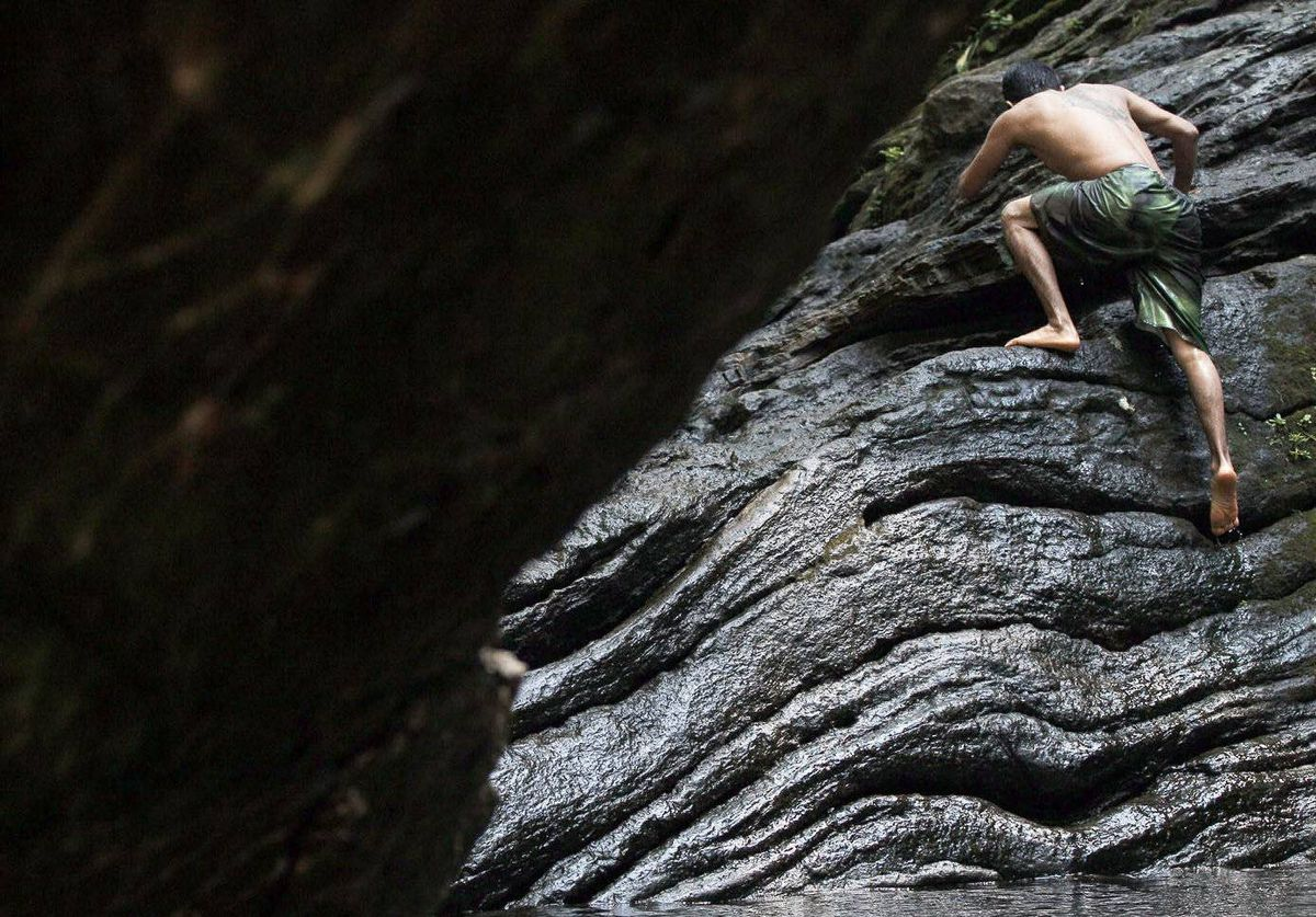 A bather climbs out of the water at the Devil's Pool in Wissahickon Valley Park in Philadelphia.