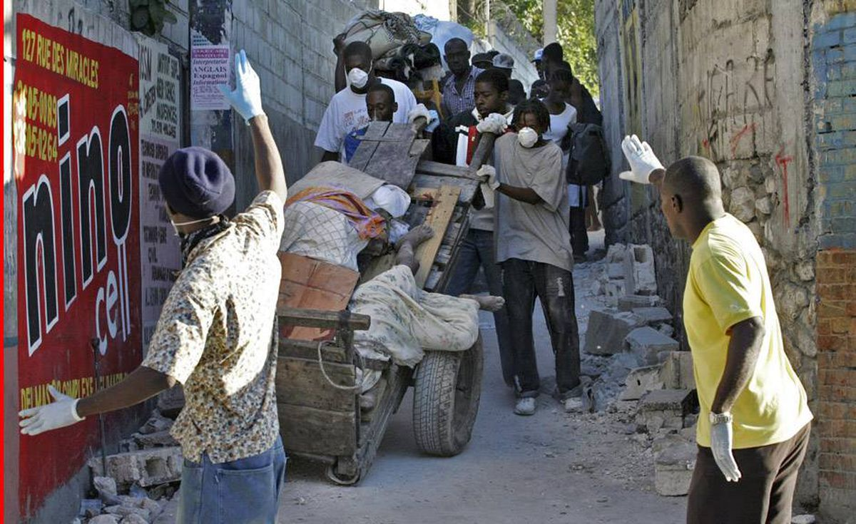 Residents carry bodies recovered from the rubble after an earthquake in Port-au-Prince today. Hundreds of bodies lay outside Port-au-Prince's General Hospital, as pick-up trucks piled with corpses continued to deliver the dead from the earthquake to a morgue there.