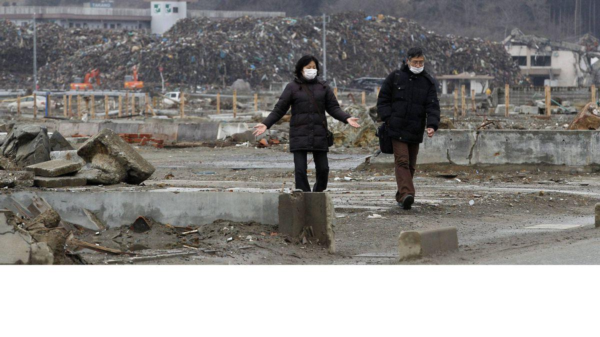 A couple walk in an area devastated by the 2011 tsunami in Minamisanriku, Miyagi prefecture, on Sunday.
