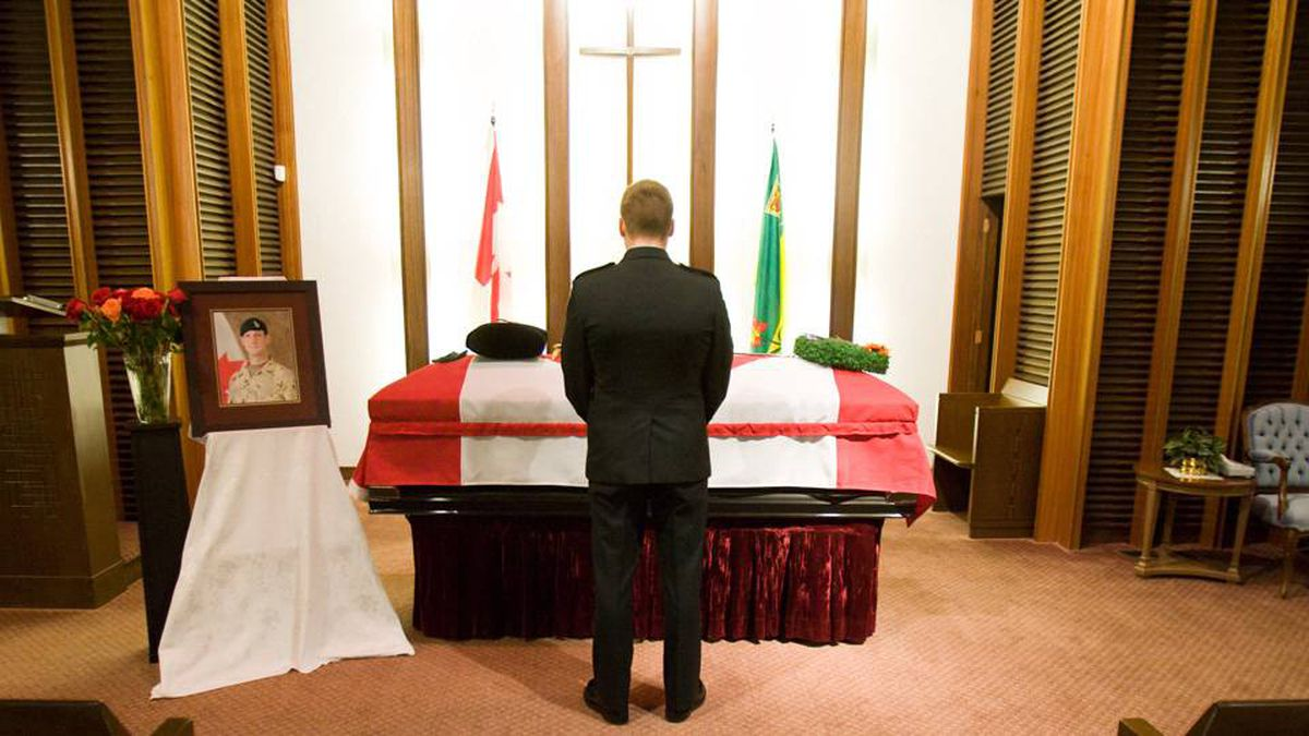 Corporal Kris Barker, a soldier with Edmonton's Princess Patricia's Canadian Light Infantry, First Battalion, who served over eight years with slain Lieutenant Justin Boyes, stands by his friend's body yesterday in Saskatoon.