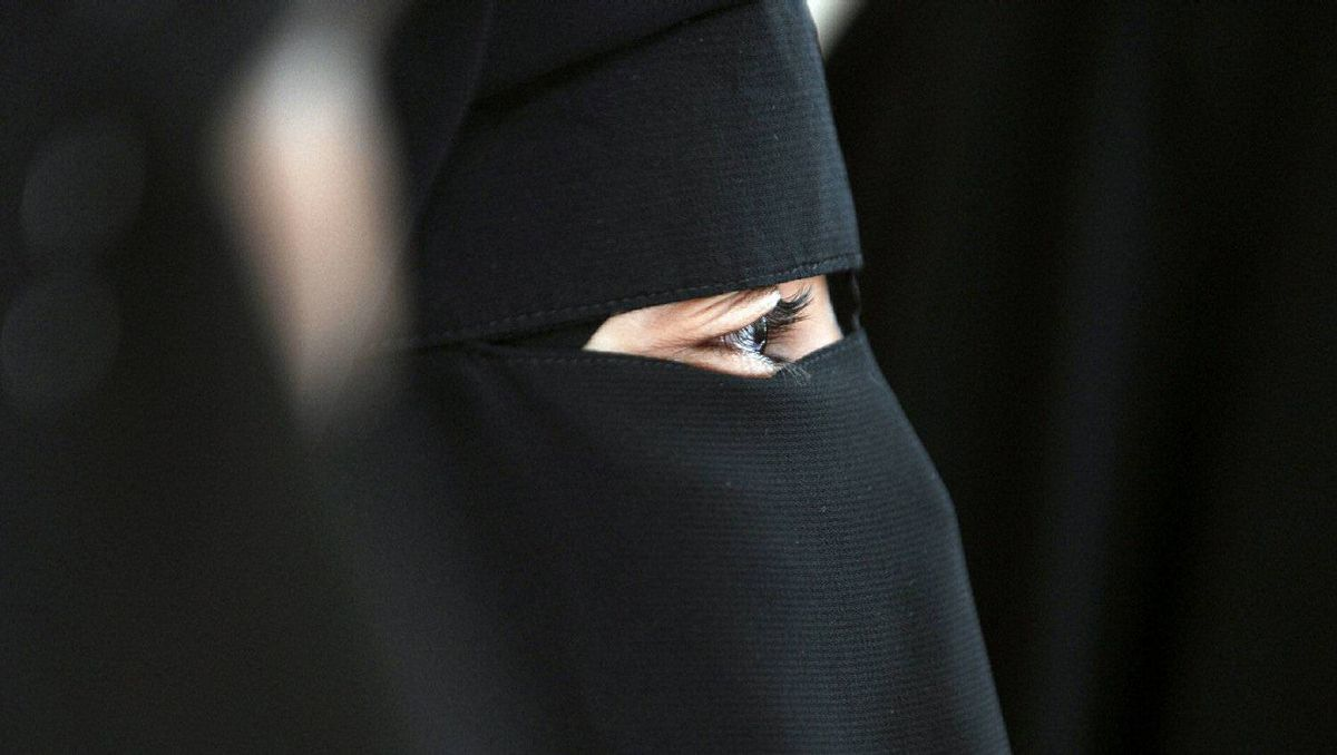A Muslim woman wearing the niqab (veil which covers the body and leaves only a small strip for the eyes) participates in a meeting with Imam Ali El Moujahed on May 18, 2010 in Montreuil, outside Paris.