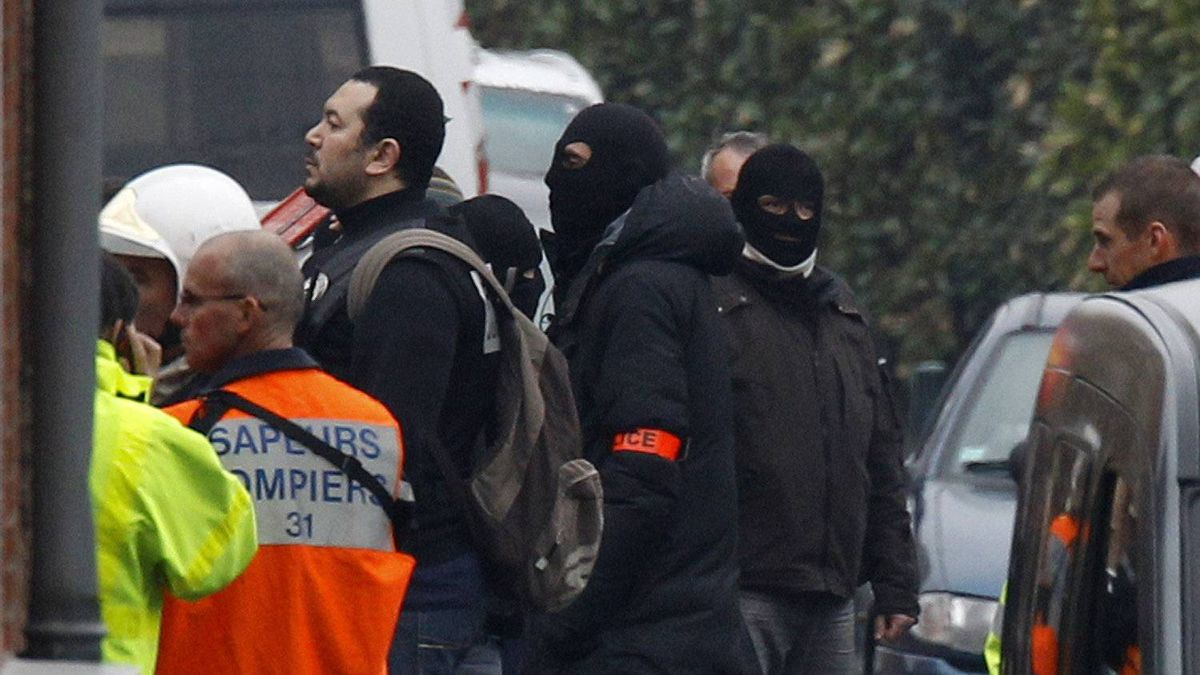 Police officers and firefighters stand near a building in Toulouse, France, Wednesday, March 21, 2012 where a suspect in the shooting at he Ozar Hatorah Jewish school has been spotted. French police exchanged fire and were negotiating Wednesday with the gunman who claims connections to al-Qaeda and is suspected of killing three Jewish schoolchildren, a rabbi and three paratroopers.