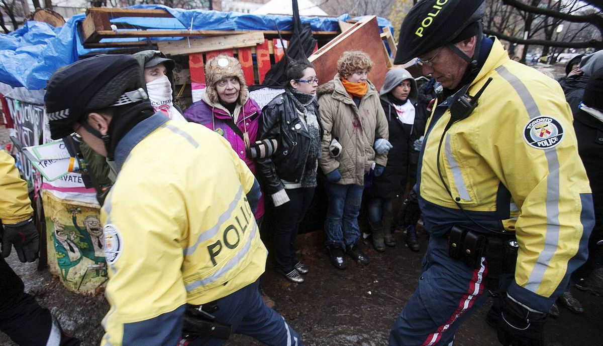 """Police walk through St. James park after they moved in to evict protesters during the """"Occupy Toronto"""" movement in Toronto"""