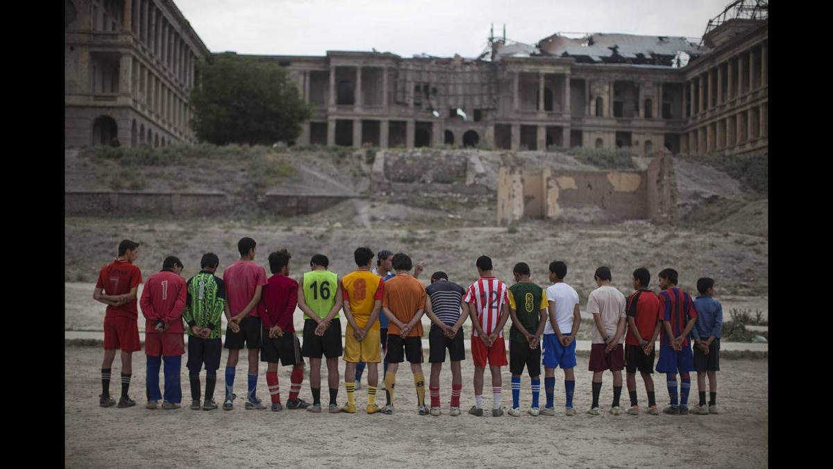 Afghans soccer players gather in front of the destroyed Darul Aman palace in Kabul, June 1, 2010.