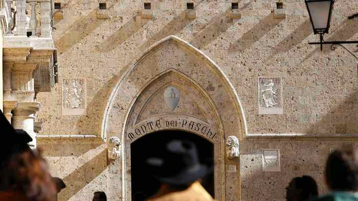 People walk towards the main entrance of the Monte dei Paschi bank headquarters in Siena