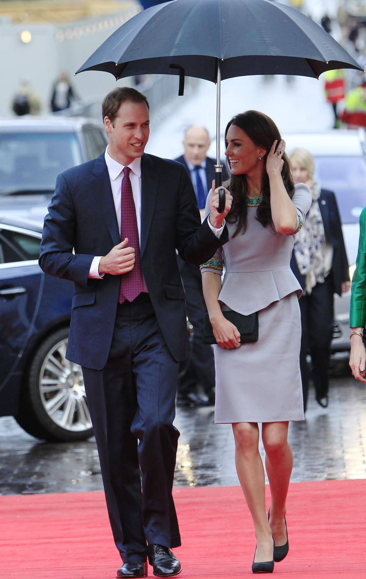 Prince William keeps her Matthew Williamson dress - complete with on-trend peplum - protected from the rain at the premiere of African Cats in London on April 25, her first public appearance in weeks.