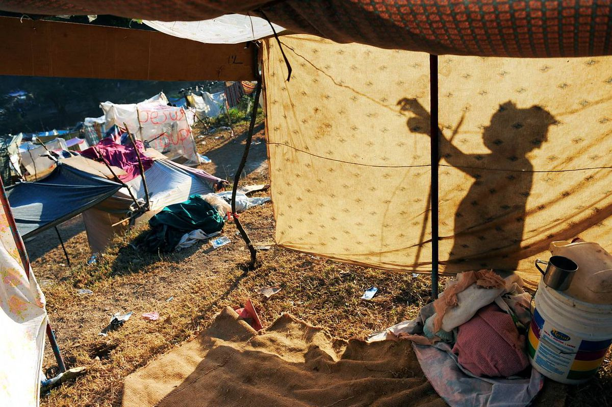 A woman constructs a shelter in a makeshift camp in Port-au-Prince on January 25, 2010. Top world officials gathered in Montreal today for emergency talks to hash out plans to rebuild Haiti, nearly two weeks after a killer earthquake devastated the impoverished nation.