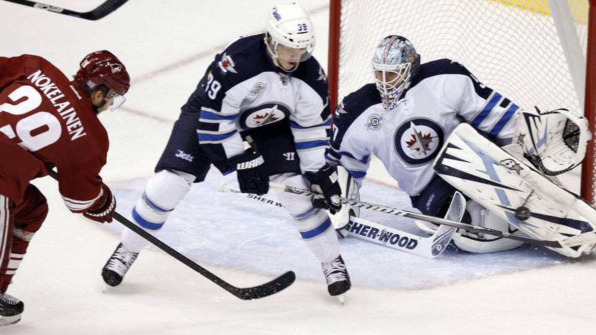 Winnipeg Jets goalie Chris Mason, right, makes a pad save on a shot from Phoenix Coyotes center Petteri Nokelainen, left, as Jets defenseman Tobias Enstrom, centre, look on in the first period of an NHL hockey game Saturday.