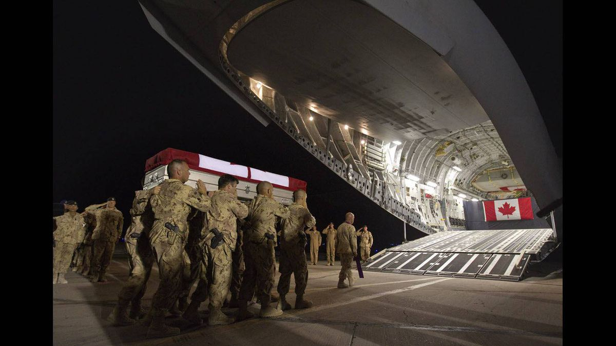 Soldiers carry the casket of Master Cpl. Francis Roy, a member of the Canadian Army's special forces regiment, to a waiting aircraft during a ramp ceremony in the early hours Tuesday, June 28, 2011 at Afghanistan's Kandahar Airfield. Roy was found mortally wounded by fellow soldiers early Saturday at a forward operating base in Kandahar city.