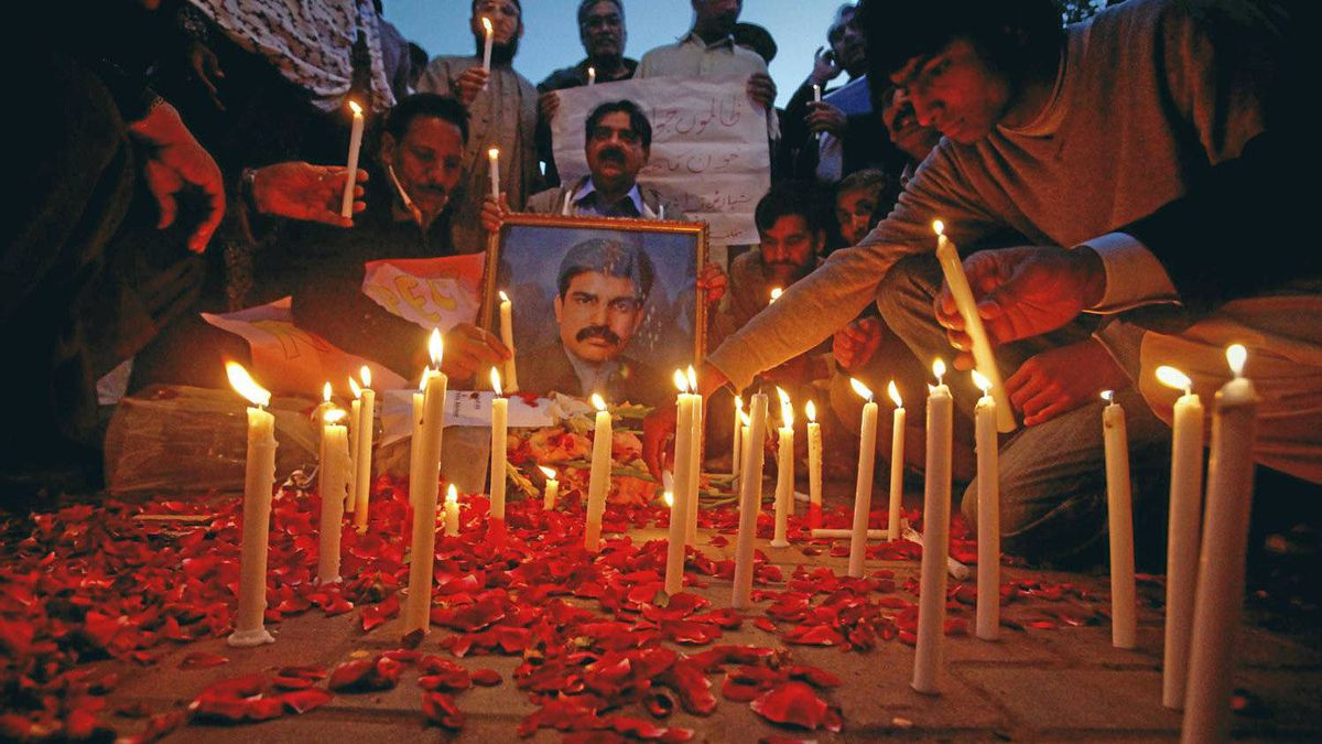 Men light candles during a candlelight vigil in commemoration of assassinated Pakistani Minister for Minorities Shahbaz Bhatti, in Lahore.