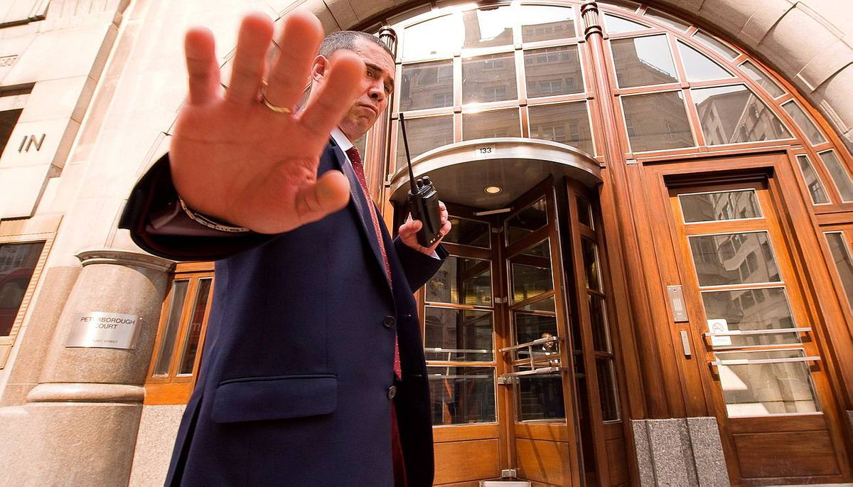 """A security guard tries to stop a photographer taking pictures of the offices of Goldman Sachs in London, on April 19, 2010. The British Financial Services Authority said Monday it was looking into US fraud charges against Goldman Sachs after Prime Minister Gordon Brown, accusing the bank of """"moral brankruptcy"""", urged a British probe."""