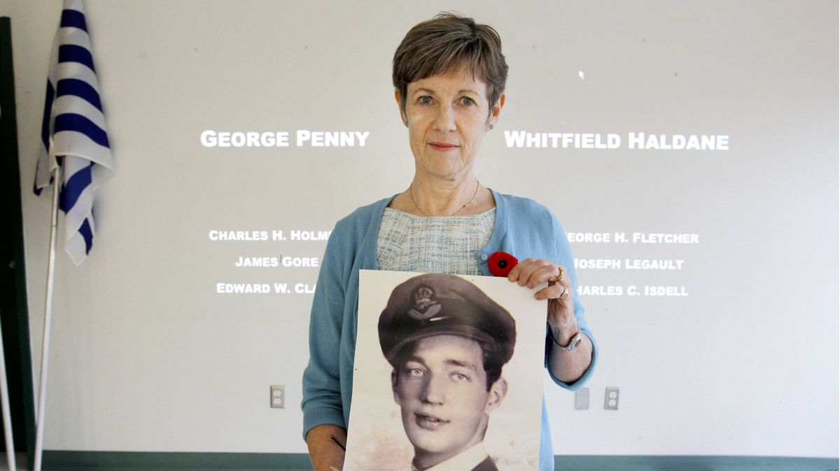 Wendy McGee holds up a photo of her Uncle, Robert Henry Rose, who died on Nov. 2, 1944 during WWII in Belgium. Wendy teaches at West Point Grey Academy in Vancouver, BC, where the students are projecting 9,700 names a day. Each name will appear simultaneously in every vigil location in Canada and Europe. More than 150 schools are participating in this remembrance project.