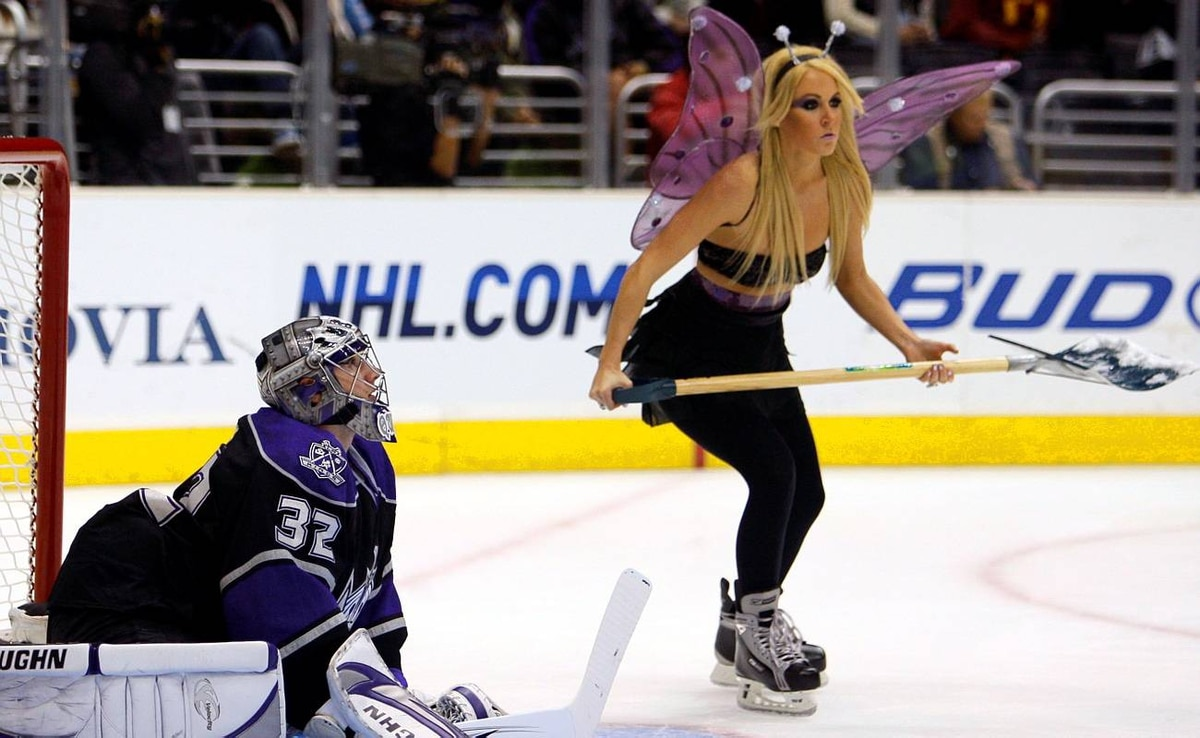 Los Angeles Kings goalie Jonathan Quick stretches during a timeout as a woman dressed in a Halloween costume cleans the ice during the first period of their NHL hockey game against the Vancouver Canucks in Los Angeles, October 29, 2009.