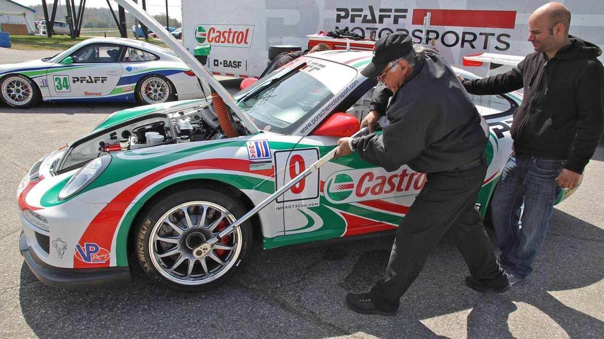 Crew chief Gianni Panico tightens a wheel on the Pfaff Motorsports car with long-handled torque wrench. Instead of conventional wheel lugs, Porsche GT3 Cup race cars use a center-lock system that clamps the wheels onto the hubs with a large, single nut. The locking nut must be torqued down with 380 foot-pounds of force - about five times the torque used on a street car with conventional wheel lugs.
