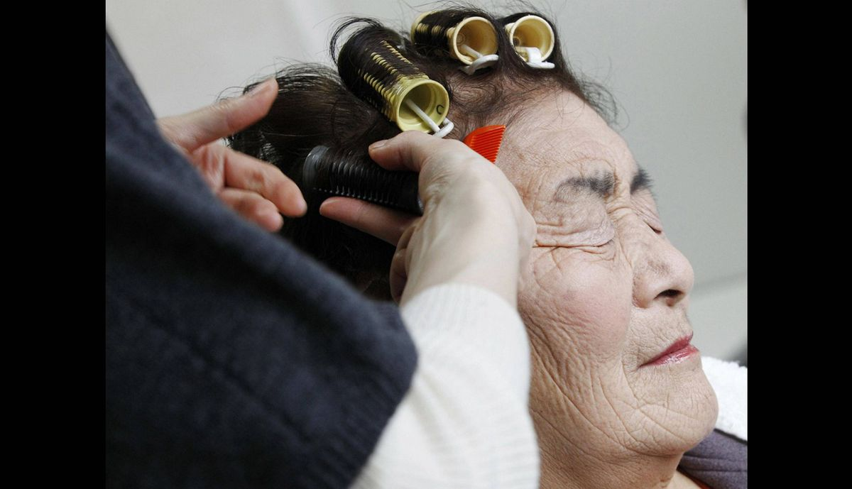 A resident has her hair done by a stylist volunteering as part of the 3.11 Portrait Project at the Midorigaoka temporary shelter in Koriyama, Fukushima prefecture in the Tohoku region, December 17, 2011. The project was conceived by photographer Nobuyuki Kobayashi who takes portraits of earthquake survivors. The portraits are then sent to schoolchildren from non-disaster areas, who frame the portraits and send them back to the survivors along with personal messages of support.