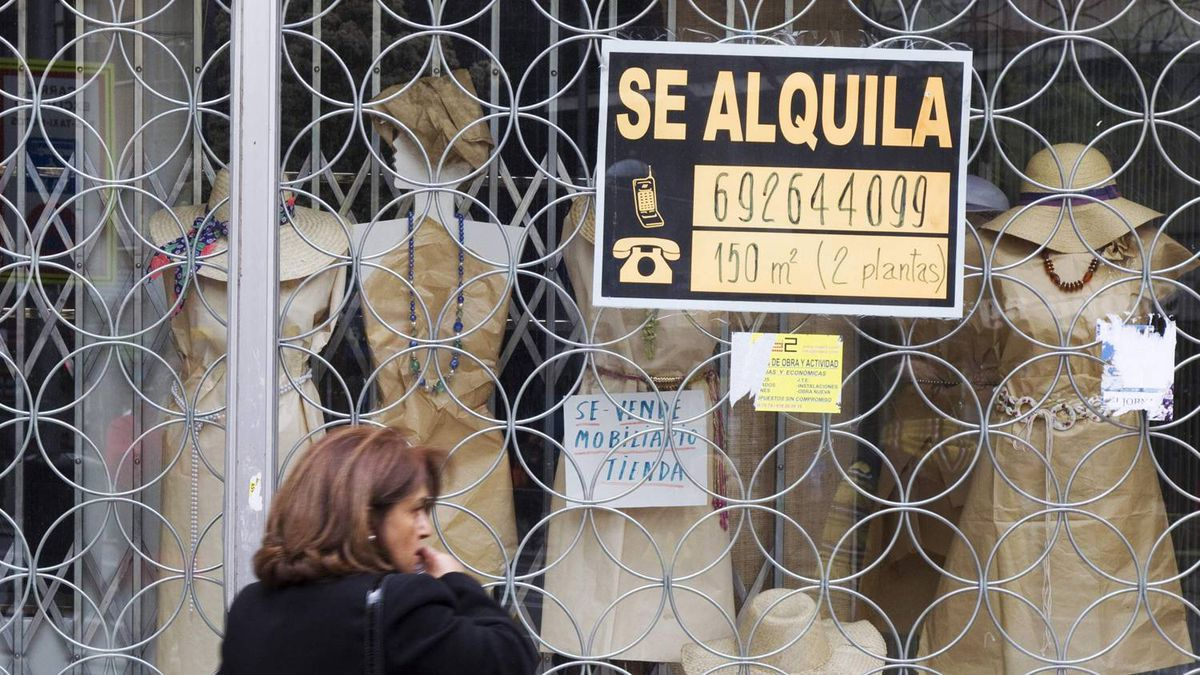"A woman passes a shop with a sign which reads ""For Rent"" in Madrid April 27, 2012."